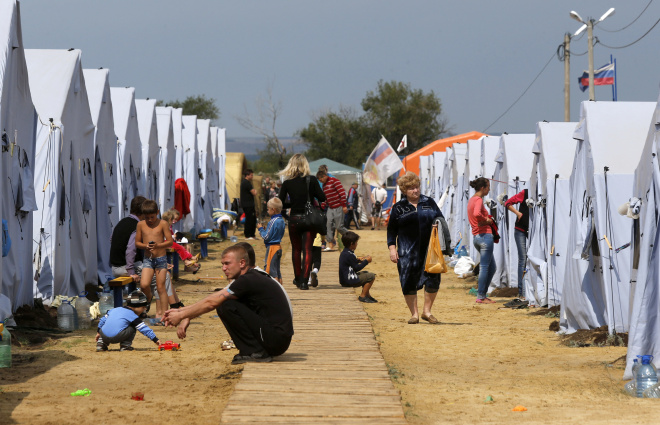 People gather at a temporary tent camp set up for Ukrainian refugees outside Donetsk, located in Russia's Rostov region near the Russian-Ukrainian border, August 18, 2014. REUTERS/Alexander Demianchuk (RUSSIA - Tags: POLITICS CIVIL UNREST CONFLICT SOCIETY) - RTR42UAL