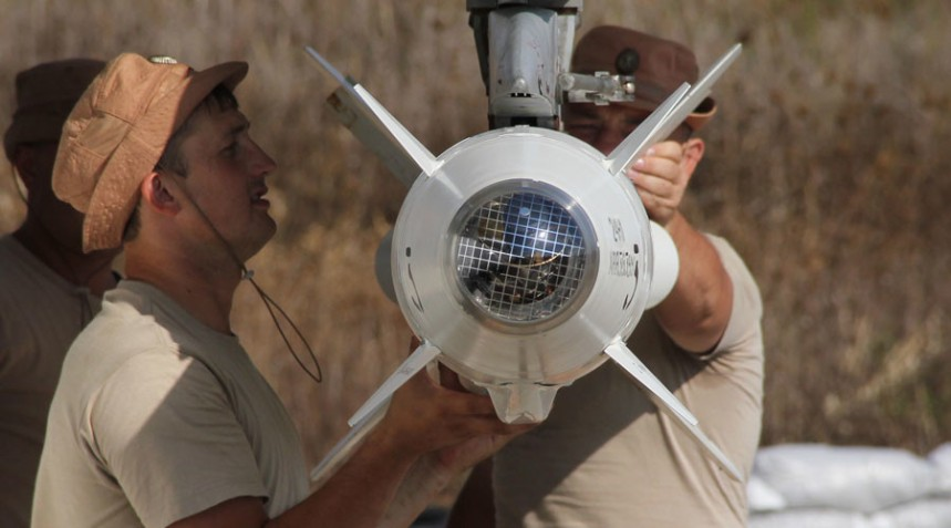 2712070 10/04/2015 Russian servicemen attach a Kh-25 high-precision missile to a Su-24 aircraft at the Khmeimim airbase in Syria. Dmitriy Vinogradov/RIA Novosti